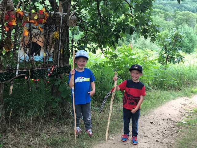 Boys with hiking sticks standing near an Art on the Trail installation